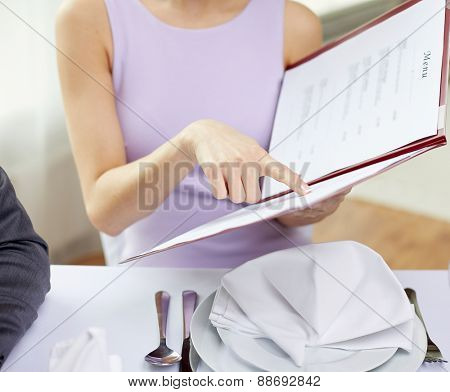restaurant, food, eating and holiday concept - close up of happy couple with menu choosing dishes at restaurant