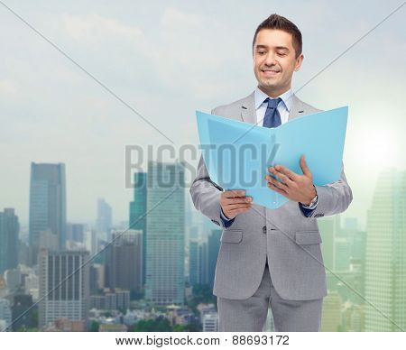 business, people, finances and paper work concept - happy smiling businessman in suit holding open folder over city background