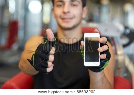 sport, bodybuilding, lifestyle, technology and people concept - happy young man with smartphone showing thumbs up in gym