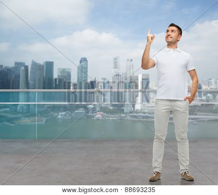 business, travel, tourism, gesture and people concept - smiling man pointing finger up over city background