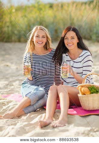 summer holidays, vacation, celebration and people concept - happy teenage girls or young women having picnic and drinking beer or lemonade on beach
