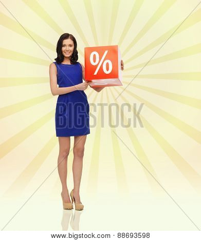 people, business, discount, shopping and consumerism concept - happy young woman in dress with red sale sign over yellow burst rays background