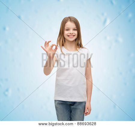 happy people and gesture concept - smiling little girl in blank white t-shirt showing ok gesture