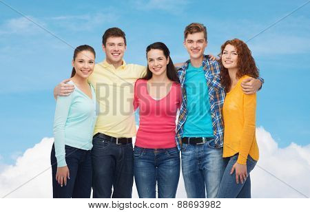 friendship, dream and people concept - group of smiling teenagers standing and hugging over blue sky with white cloud background