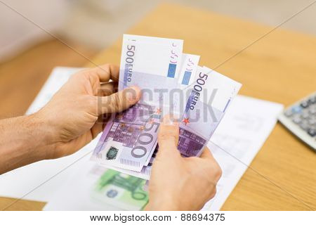savings, finances, economy and home concept - close up of man hands counting money at home
