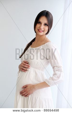 Pregnant woman on white wall background