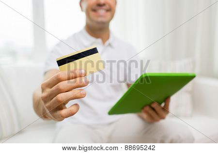 technology, people and lifestyle, distance learning concept - close up of happy man with credit card and tablet pc computer at home