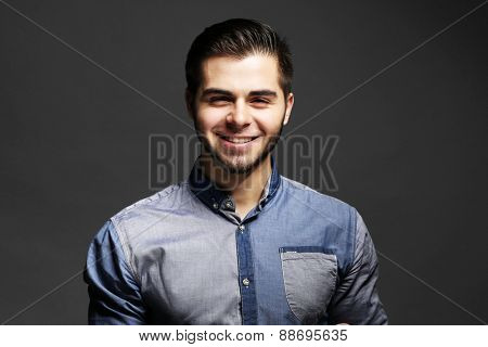 Portrait of young man in blue shirt on gray background