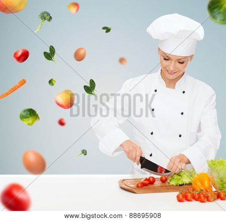 cooking and food concept - smiling female chef, cook or baker chopping vegetables over gray background