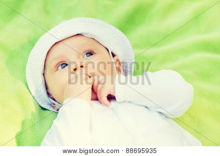 child, childhood and toddler concept - little baby lying on blanket and looking up