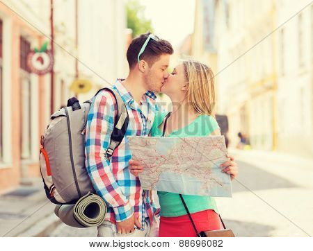 travel, vacation, love and friendship concept - smiling couple with map and backpack in city