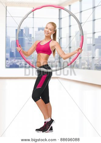 fitness, sport, people and healthcare concept - young sporty woman exercising with hula hoop over gym background