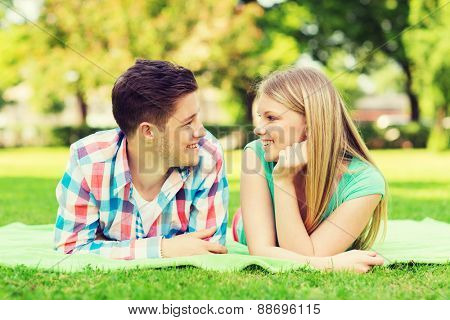 holidays, vacation, love and friendship concept - smiling couple lying on blanket and looking at each other in park