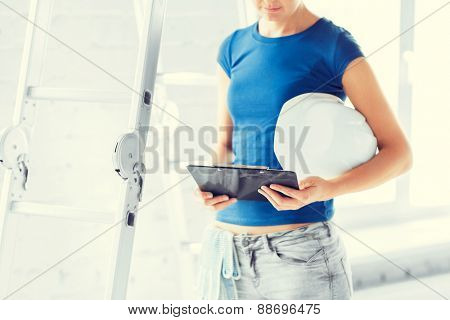 architecture and home renovation concept - woman architect with helmet and blueprint