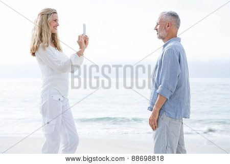 Happy couple taking pictures with mobile phone at the beach