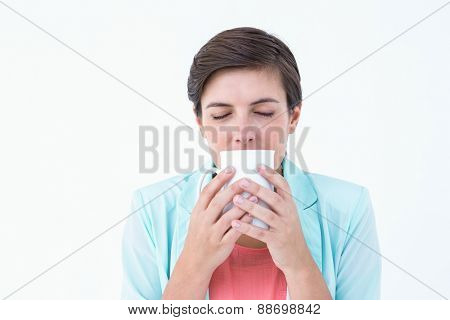 Casual brunette drinking coffee on white background