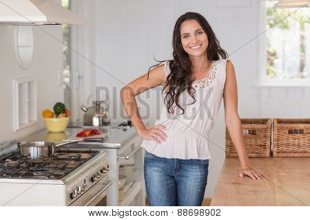 Beautiful brunette smiling at camera in the kitchen