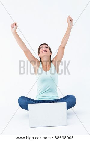 Excited woman with laptop raising her arms on white background