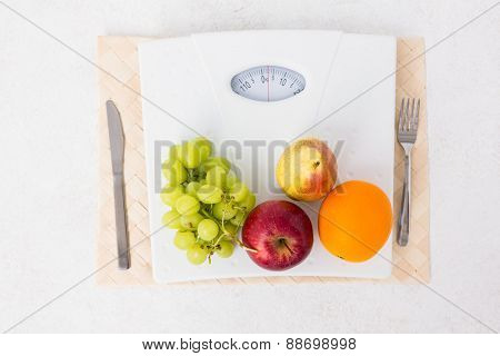 Weighing scales with fruits on white background