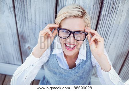 Pretty blonde woman smiling at the camera on wooden background