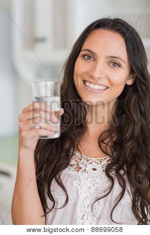 Pretty brunette drinking glass of water in the kitchen