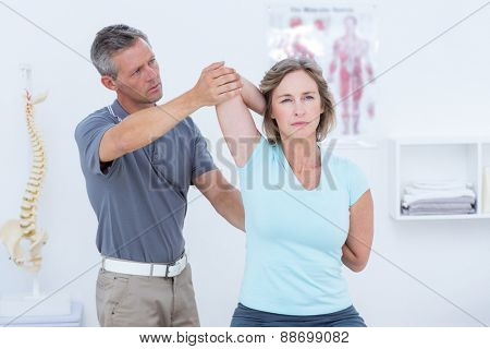 Woman stretching her arms in medical office