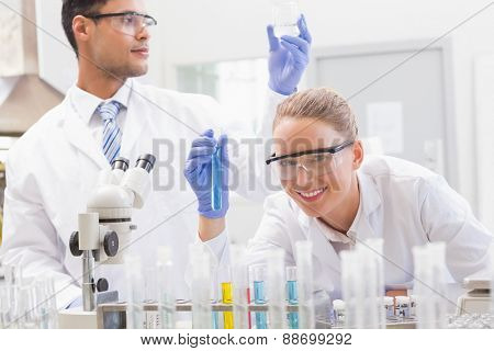 Smiling scientists examining test tube and beaker in laboratory