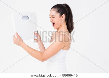 Fit woman holding weighing scales on white background