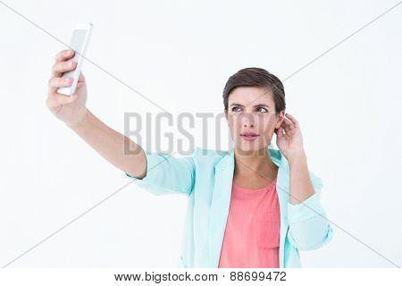 Pretty woman taking photo on white background