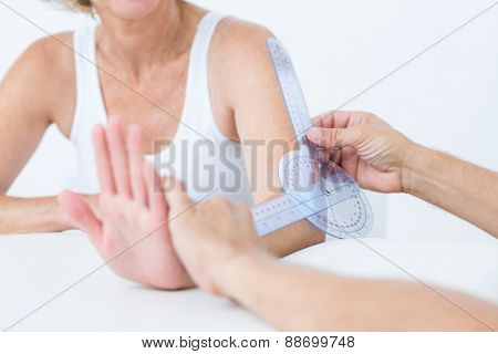 Doctor measuring elbow with goniometer in medical office
