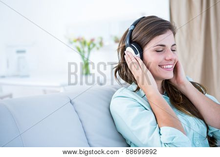 Peaceful woman listening music at home in the living room