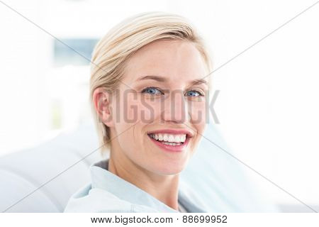 Pretty blonde woman relaxing on the couch and looking at the camera in the living room