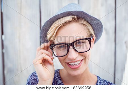 Pretty blonde woman wearing hipster glasses on wooden background