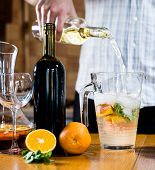 picture of sangria  - Man pouring white wine into a jar - JPG