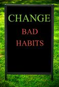 image of  habits  - CHANGE BAD HABITS message on sidewalk blackboard sign against green grass background - JPG