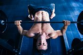 stock photo of bench  - Muscular man workout with barbell on bench at gym - JPG