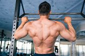 stock photo of pull up  - Back view portrait of a handsome muscular man pulling up at gym - JPG