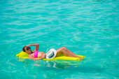 picture of mattress  - Woman relaxing on inflatable mattress at the beach - JPG