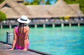 foto of jetties  - Beautiful woman sitting on wooden jetty at tropical resort - JPG