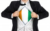 foto of ivory  - businessman showing Ivory Coast flag underneath his shirt over white background - JPG