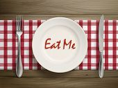 stock photo of eat me  - top view of eat me written by ketchup on a plate over wooden table - JPG
