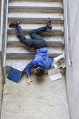 stock photo of slip hazard  - business man falling down set of stairs - JPG
