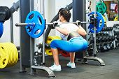 stock photo of heavy  - fitness woman doing exercises for back muscles and buttocks with heavy weight - JPG