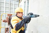 stock photo of tile cladding  - worker builder making construction for ventilation facade on a building with screwdriver drill - JPG