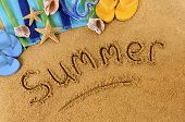 stock photo of summer beach  - The word Summer written on a sandy beach with scuba mask beach towel starfish and flip flops - JPG