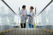 stock photo of escalator  - Vietnamese medical workers discussing diagnosis while standing on the escalator - JPG