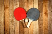 stock photo of ping pong  - Ping pong paddles and ball on wooden background - JPG
