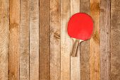 stock photo of ping pong  - Red paddle for ping pong on wooden background - JPG