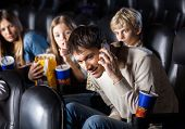 stock photo of annoying  - Annoyed family looking at man using mobilephone in cinema theater - JPG