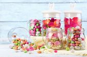 stock photo of jar jelly  - Multicolor candies in glass jars on color wooden background - JPG